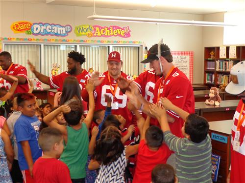 49ers high five Lakewood students after reading to them in the library