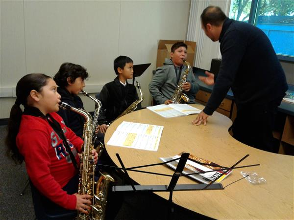 students practice playing their saxophones