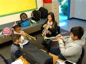 students follow teacher in practicing trumpets