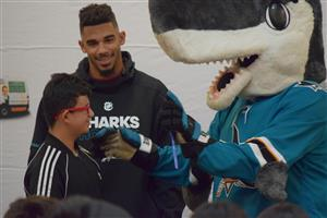 Evander Kane and SJ Sharkie hand out glasses to students